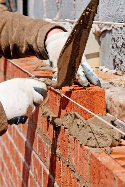 Eugene Worker Brick Laying with gloves on and a clay spatula